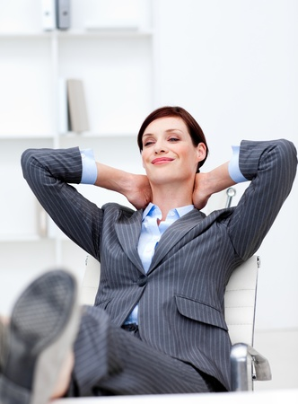 Businesswoman sitting in office with feet on desk relaxing  photo