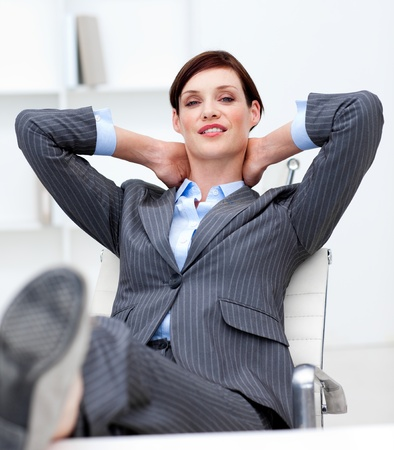 Businesswoman leaning back on a chair with his feet on the desk photo