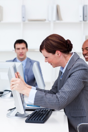 Businesswoman getting frustrated with a computer at work photo
