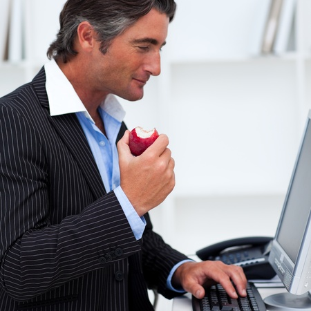 Close-up of a happy businessman eating a red apple photo