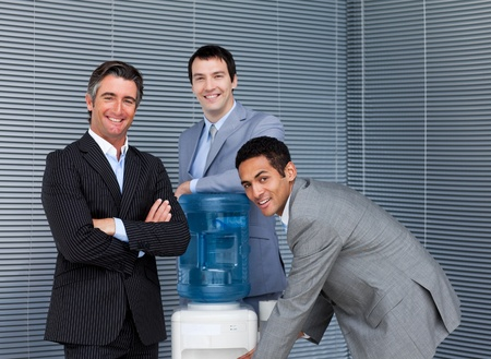 man drinking water: Multi-ethnic business team at water cooler