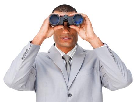 Serious young businessman looking through binoculars  photo