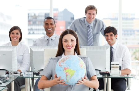 terrestrial globe: Pretty businesswoman and her team showing a terrestrial globe