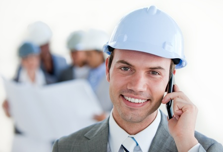 Smiling arhitect with a hardhat on phone
