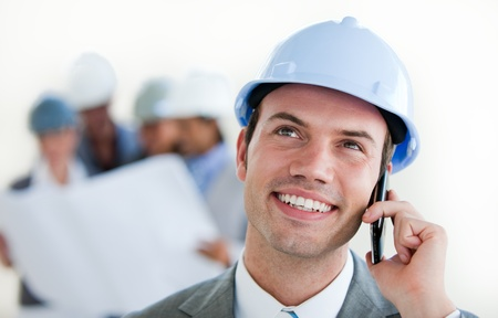 site manager: Focus on a male arhitect with a hardhat on phone Stock Photo