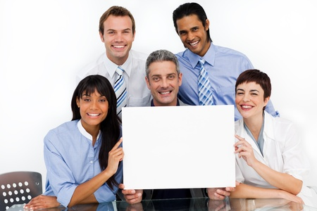 A business group showing diversity holding a white card photo