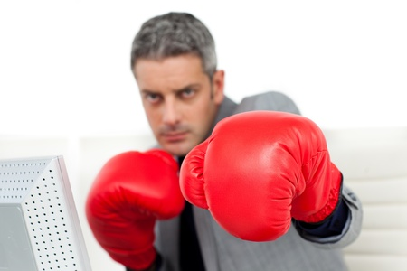Self-assured businessman with boxing gloves  photo