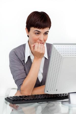 Stressed attractive businesswoman sitting at her desk photo