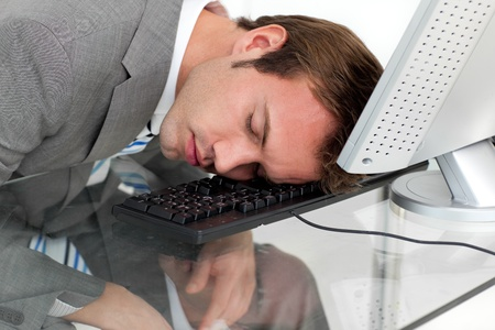 Close-ep of a tired businessman sleeping on his desk  photo