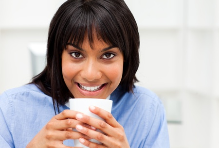 Radiant businesswoman drinking a coffee  photo