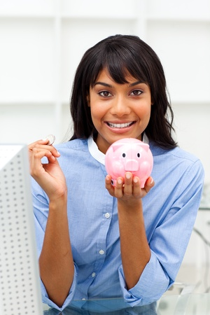 Smiling businesswoman saving money in a piggybank  Stock Photo - 10110222