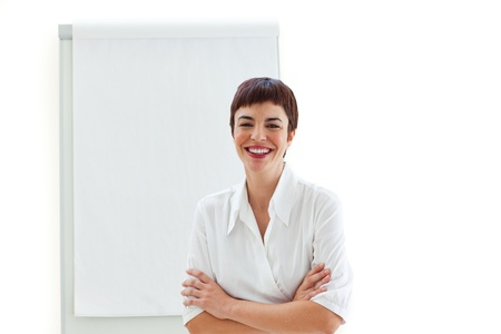 Laughing businesswoman with folded arms in front of a board Stock Photo - 10091682