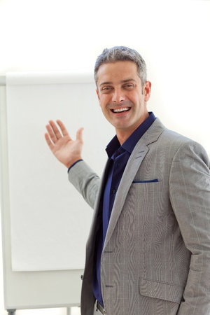 Cheerful mature businessman pointing at a board  photo