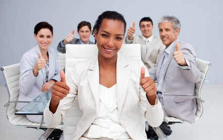 Afro-American businesswoman and her team with thumbs up photo