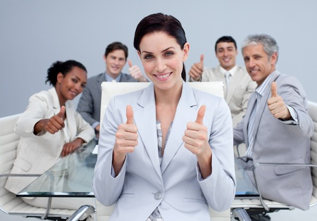 Happy business team with thumbs up photo