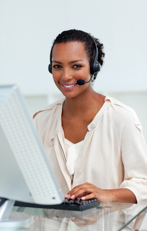 Afro-american businesswoman with headset on working at a computer photo