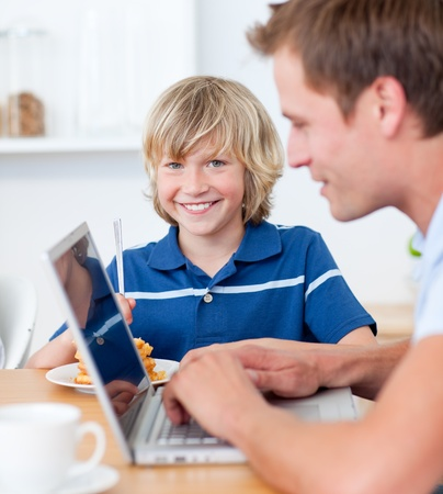 Adorable boy having breakfast while his father using a laptop photo