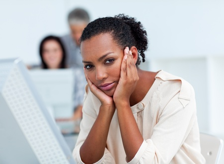 Bored young businesswoman at her desk Stock Photo - 10095719
