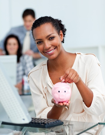 Smiling businesswoman saving money in a piggy-bank Stock Photo - 10095328