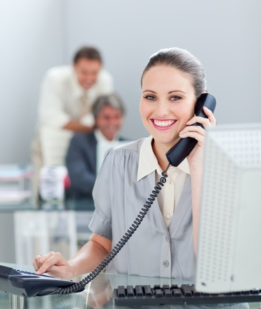 Charismatic businesswoman on phone working at a computer Stock Photo - 10093080