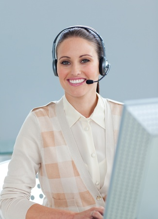 Charming businesswoman with headset on working at a computer photo
