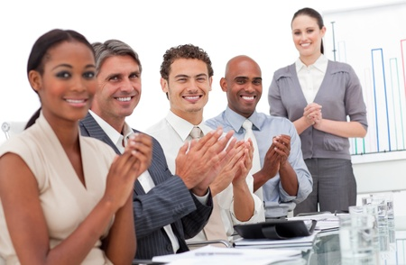 Happy business team applauding a good presentation photo