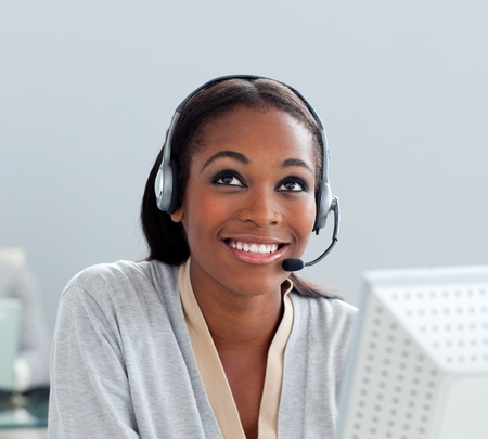 Delighted businesswoman using headset at her desk photo