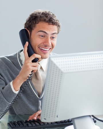 Charming businessman on phone at his desk  photo