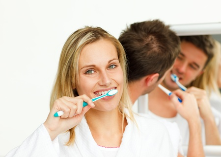 Young woman cleaning her teeth with her boyfriend photo
