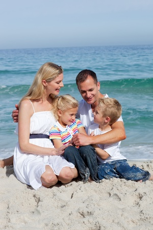 Portrait of an affectionate family sitting on the sand  photo