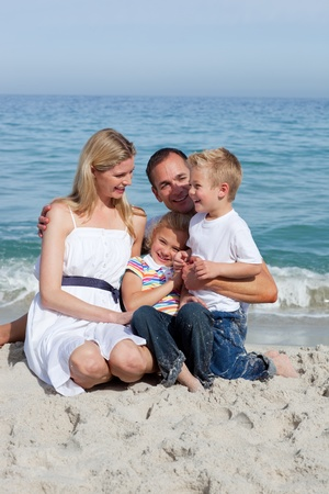 Happy children and their parents sitting on the sand  photo