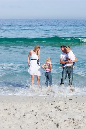 Cheerful family having fun at the beach photo