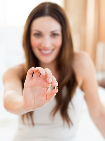 bolus: Smiling woman taking a pill sitting on bed