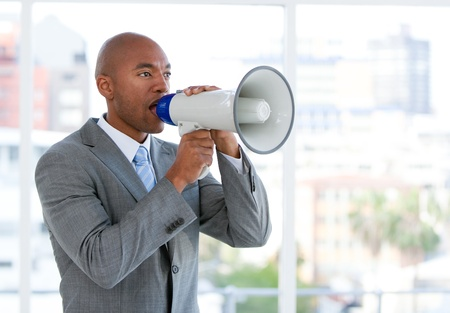 Ambitious businessman yelling through a megaphone photo
