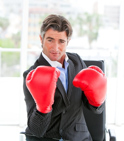 assertive: Self-assured businessman wearing boxing gloves