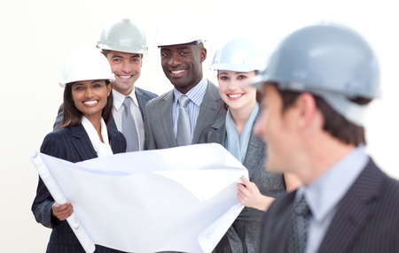 Engineer looking at his team studying a plan photo