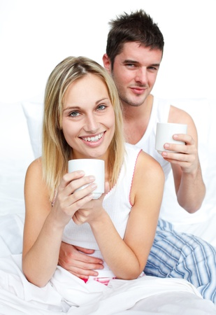Couple drinking coffee in bed and smiling at the camera photo
