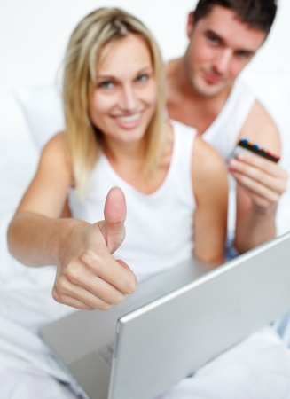 Couple in bed buying on-line successfully photo