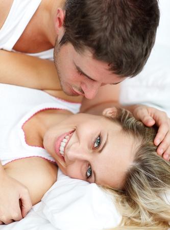 страстный: Человек, ласкать его grilfriend на постели Фото со стока
