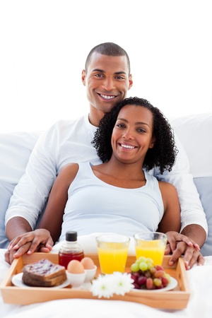 Afro-american couple having breakfast lying on their bed