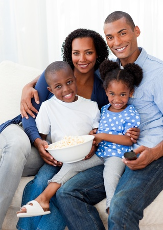 Portrait of a family eating popcorn and watching TV photo