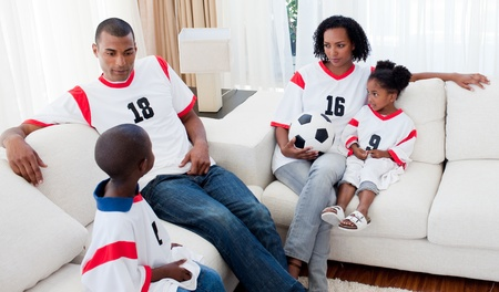 Afro-american family watching a football match photo