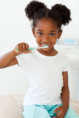 Portrait of a smiling little girl brushing her teeth photo