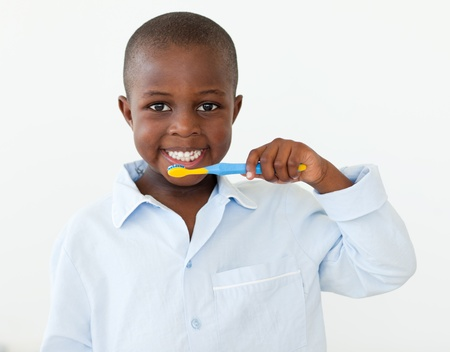 Portrait of a smiling little boy brushing his teeth photo