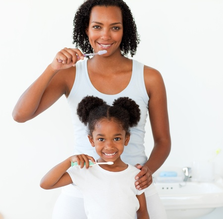 Mother and her daughter brushing their teeth photo