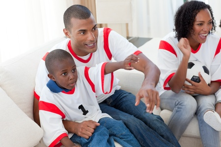 Excited Afro-American family wathing a football match  photo