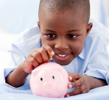 sympathetic: Young Boy on a bed putting money into a piggy bank