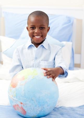 terrestrial globe: Cute little boy holding a terrestrial globe