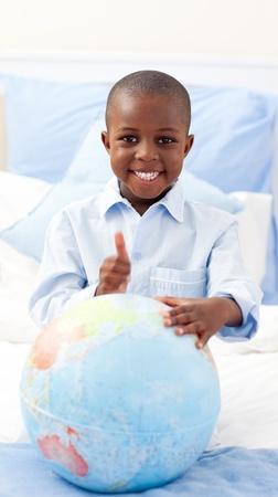 terrestrial globe: Smiling little boy holding a terrestrial globe