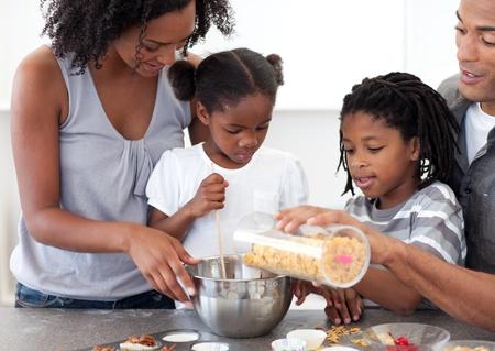 hombre cocinando: Familia �tnica haciendo galletas juntos